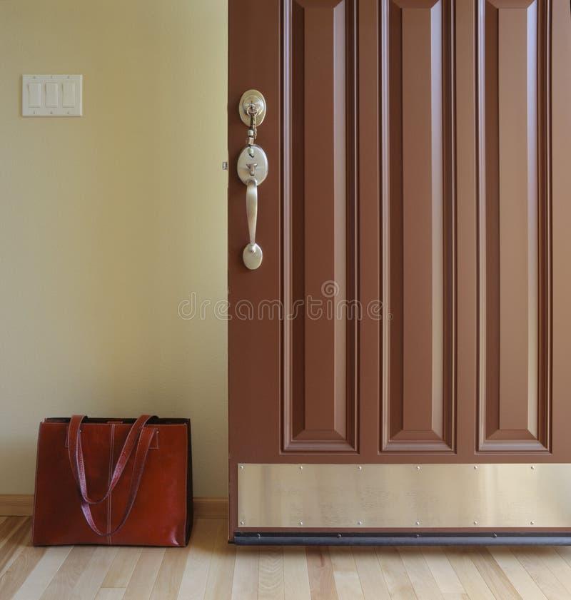 房子开放大门有公文包简要的袋子的在词条 回家从或离开工作概念的 免版税库存照片