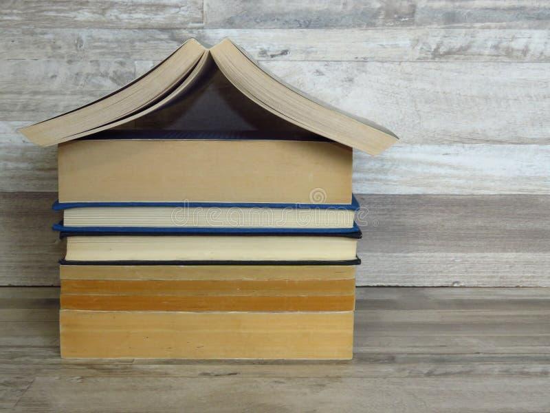 房子形状的堆在灰色白色被漂白的橡木架子背景的旧书 库存图片