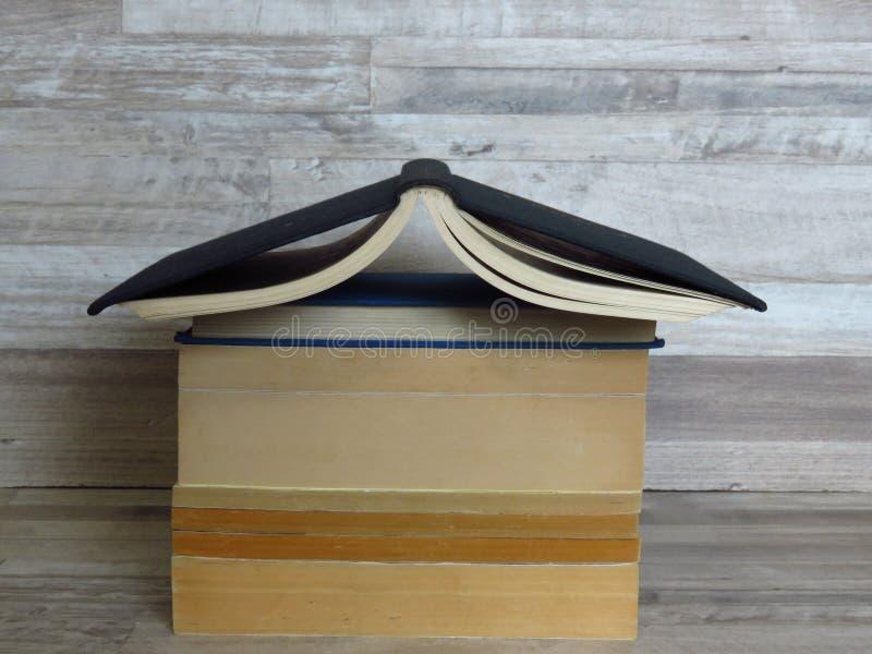 房子形状的堆在被漂白的橡木背景的旧书 免版税库存图片