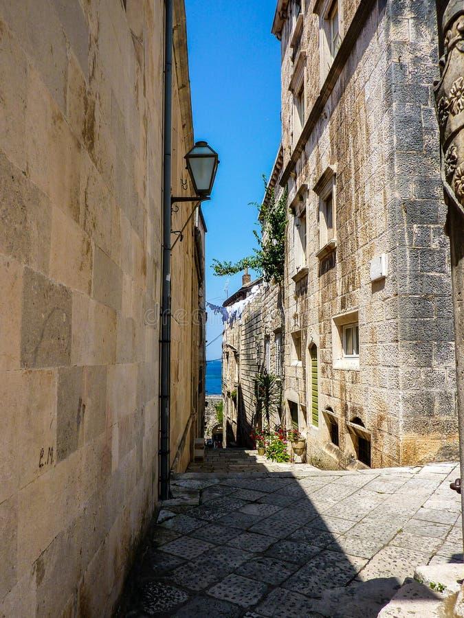 房子排行的狭窄的街道与在科尔丘拉,克罗地亚退出和海的看法 库存照片