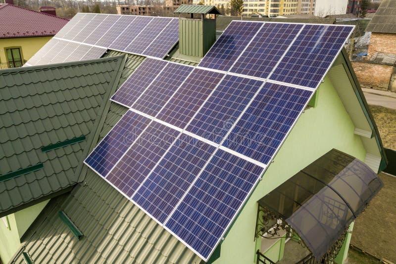 房子村庄鸟瞰图与蓝色发光的太阳照片流电盘区系统的在屋顶 可更新的生态绿色能量 库存图片