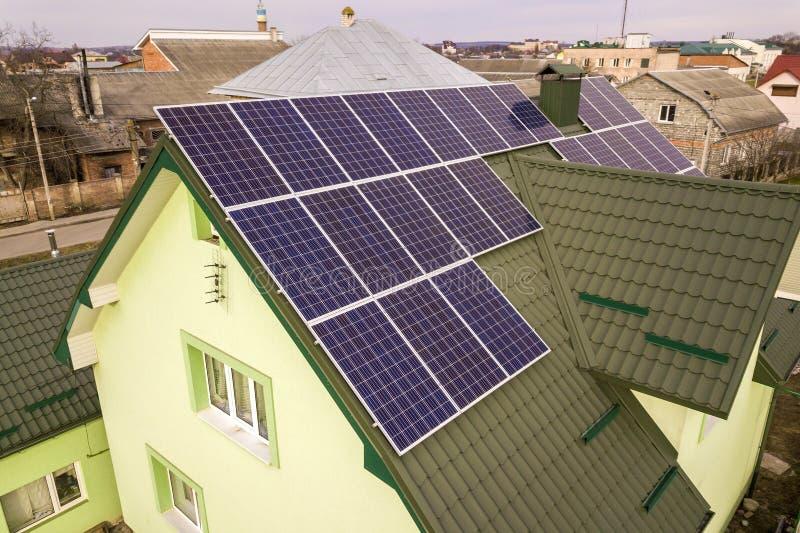 房子村庄鸟瞰图与蓝色发光的太阳照片流电盘区系统的在屋顶 可更新的生态绿色能量 免版税库存图片