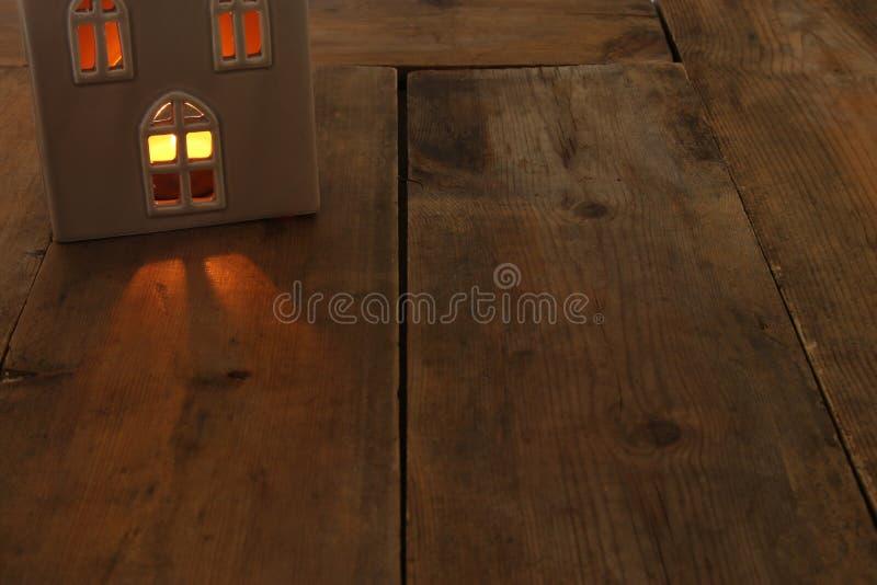 房子灯笼的低调图象有灼烧的蜡烛和温暖的光的在老木背景的窗口里 免版税库存图片