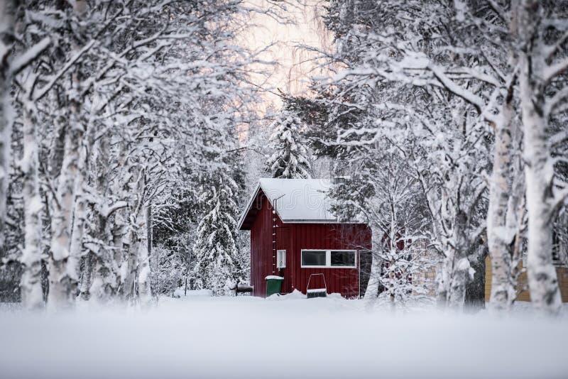 房子用暴雪和日落时间盖了在冬天季节在假日村庄Kuukiuru,芬兰 免版税库存图片