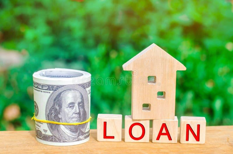 房子的模型,金钱和题字`贷款` 买债务的一个家 家庭房地产投资和风险管理 免版税库存图片