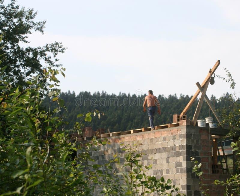 房子的设施 建造者在屋顶运作 砖放置 免版税图库摄影