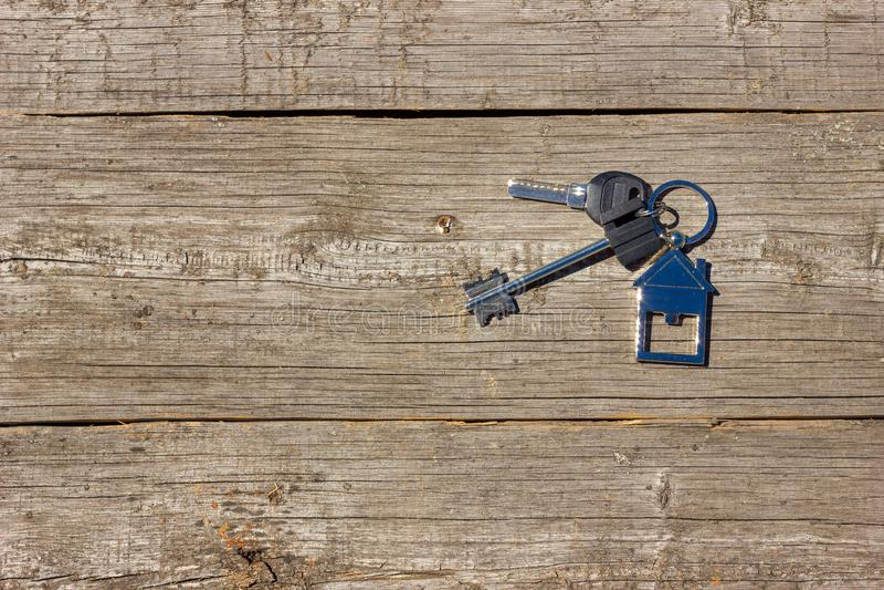 房子的钥匙在木背景,买物业的概念说谎 免版税图库摄影