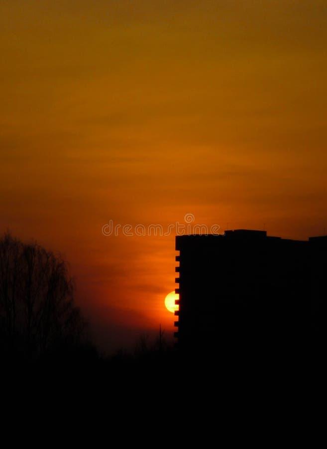 房子的黑剪影反对明亮的橙色日落的 太阳美妙地设置 日落的看法 免版税库存照片