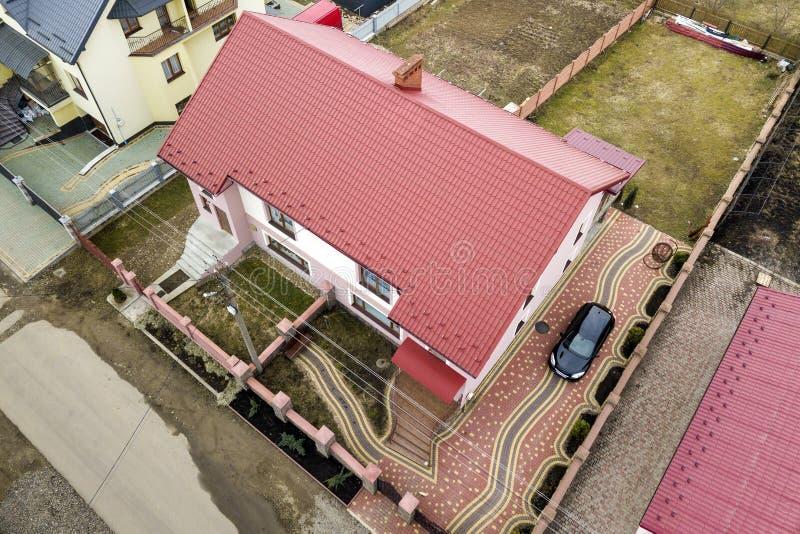 房子空中顶视图有木瓦屋顶和砖烟囱的在安静的邻里,在被铺的围场的黑汽车 很好维护 免版税库存图片