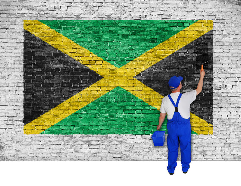 房屋油漆工用牙买加的旗子盖砖墙 免版税库存图片
