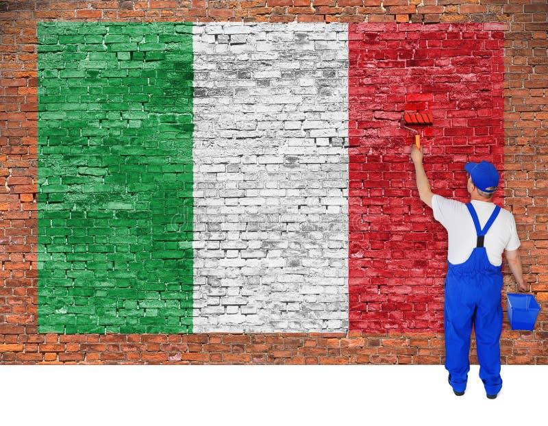 房屋油漆工绘意大利的旗子在砖墙上的 库存图片