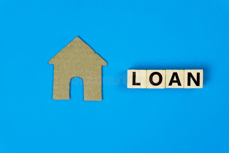 房屋贷款概念 纸做的一个小屋模型切开用木块在蓝色背景 描述修造的贷款或 免版税库存图片