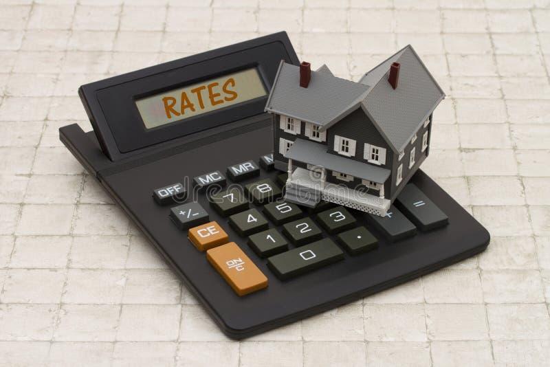 房屋贷款利率, A灰色房子和计算器在sto 免版税库存照片