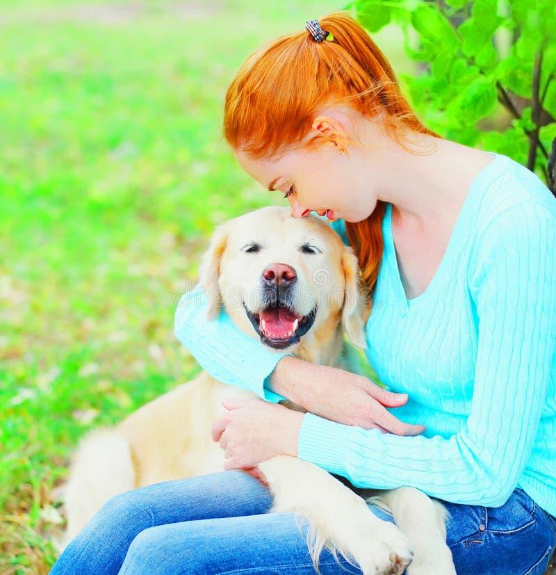所有者妇女拥抱她的金毛猎犬狗 免版税图库摄影