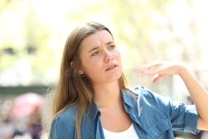 扇动与手痛苦中风的不快乐的妇女 免版税图库摄影