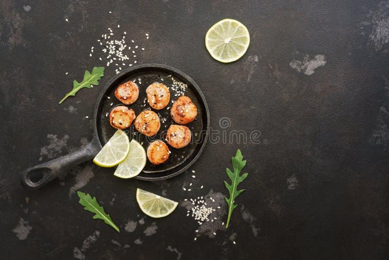 扇贝在一个平底锅油煎了用柠檬,在黑石背景 顶视图,拷贝空间 免版税库存照片
