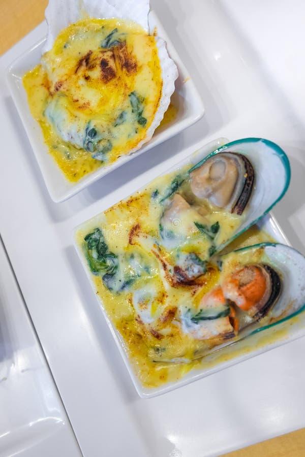 扇贝和淡菜烘烤了用乳酪和菠菜 免版税库存图片