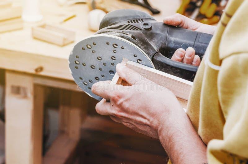 手一个人擦亮与一台磨床的一个木部分 鲤鱼 免版税库存照片