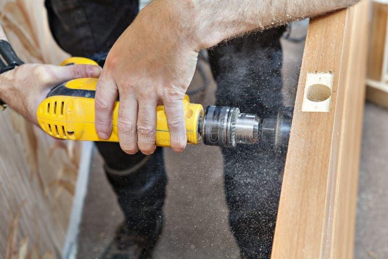 手与电钻,门锁乏味的大孔一起使用  库存照片