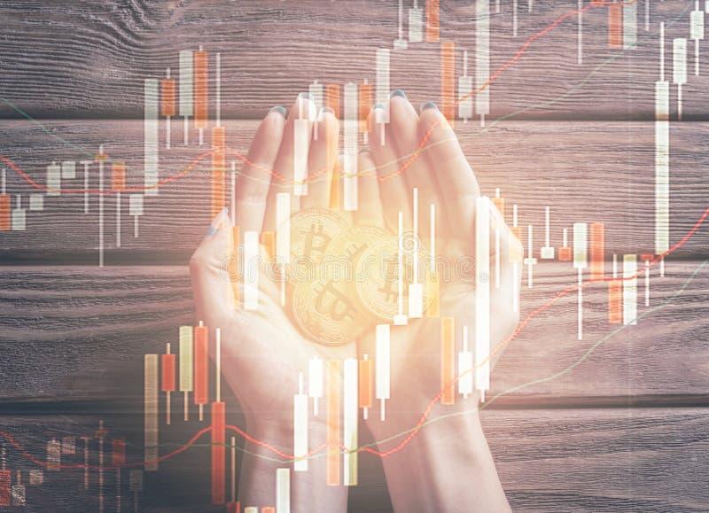 手两次曝光有bitcoins和图的 免版税库存图片