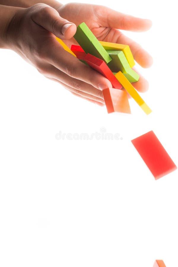 手中下跌的五颜六色的多米诺 免版税库存照片