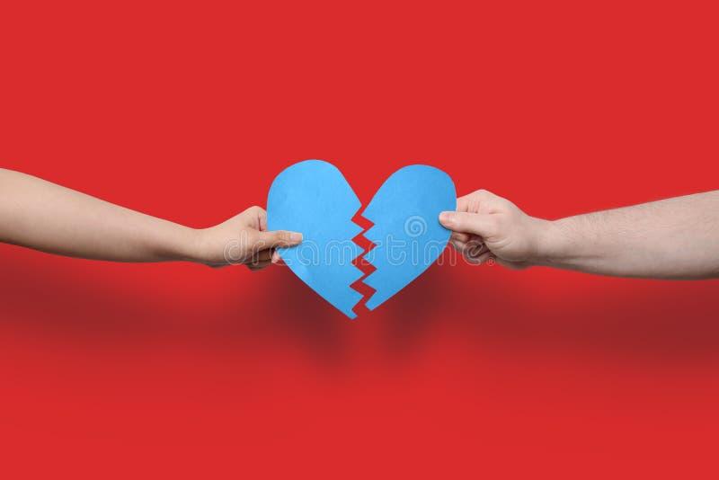 手中蓝的碎心,红色背景上剪掉的纸 免版税库存照片