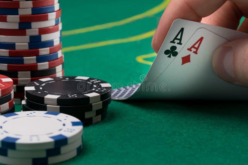 手为在一张绿色啤牌桌上的两张赢得的卡片上升 免版税库存图片