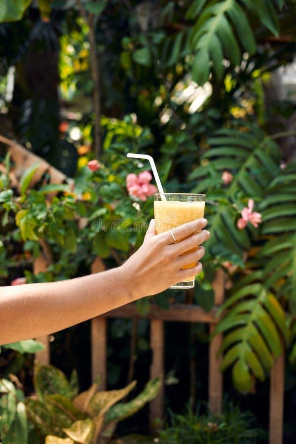 手举行健康菠萝圆滑的人鸡尾酒 免版税库存照片