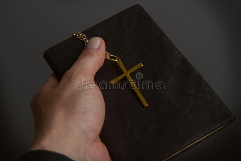 手举行十字架和Biblie 免版税库存照片