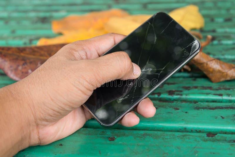 手举行和重击在残破的流动智能手机接触在室外公园sceen 库存图片