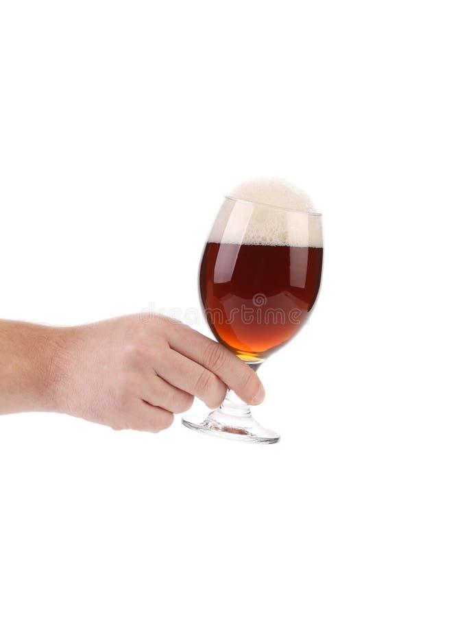 手举行杯黑啤酒 免版税库存照片