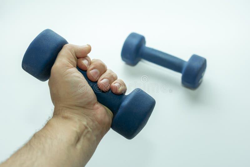 手举行演奏的体育一个蓝色哑铃,另一个哑铃说谎附近, 免版税库存图片