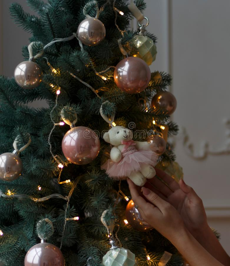 手举行玩具 与桃红色玩具和崽的圣诞树,为假日做准备 圣诞节森林上了凸边早晨多雪的线索宽冬天 免版税库存照片