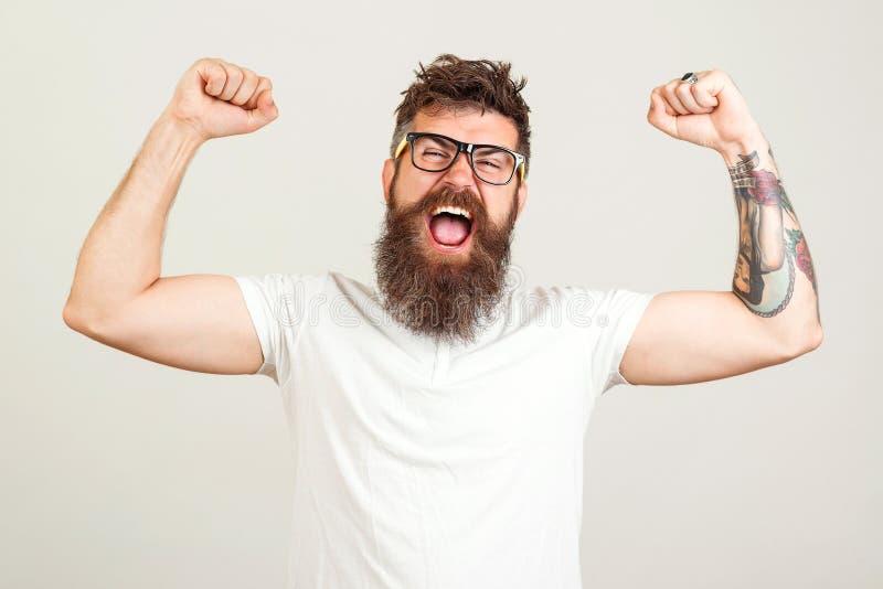 手举起大呼大叫的蓄须野人 戴着眼镜庆祝成功的兴奋蓄胡子 目标,赢家,庆祝 脸 免版税图库摄影