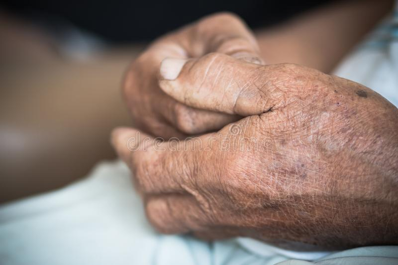 手亚裔年长人掌握他的手、更旧的起皱纹的手在单独坐在他的房子里的祷告,世界仁慈天概念和 免版税库存图片