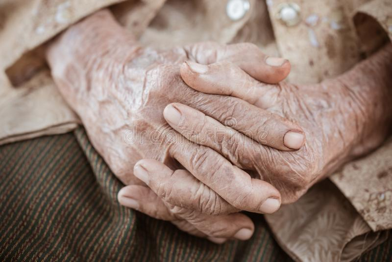 手亚裔年长妇女掌握她的在膝部,对的手在单独坐在他的房子,世界里的祷告的年长起皱纹的手 免版税图库摄影