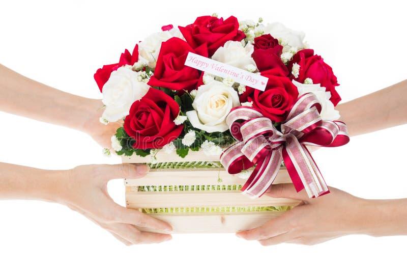 手交付红色和白色玫瑰花篮子  图库摄影