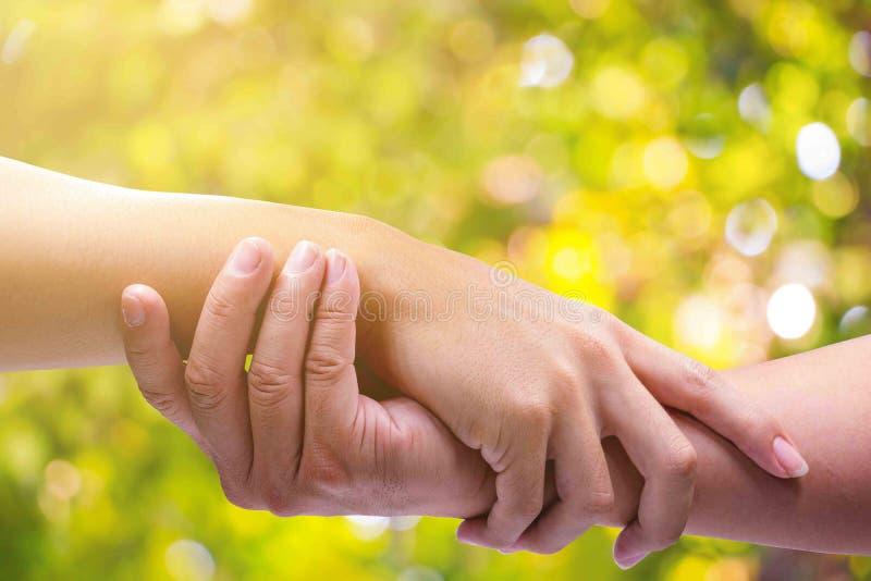 手人握手在绿色bokeh背景的 库存照片