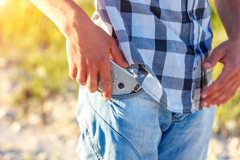 手从他的牛仔裤口袋里面拉电话 库存照片