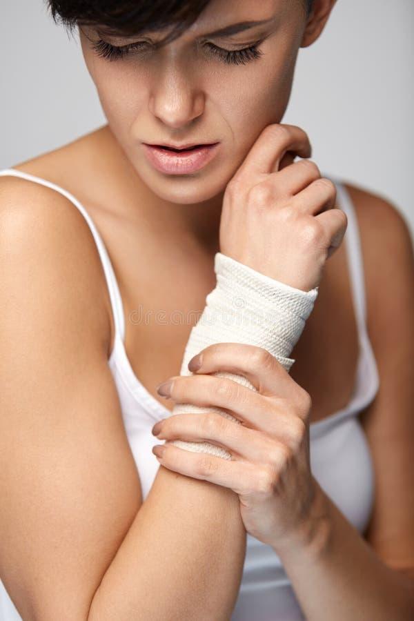 手伤 有在手边感觉痛苦的绷带的美丽的妇女 库存图片