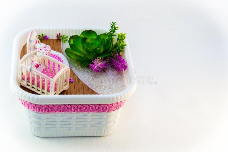 手佣人,有一个轻便小床的一间爱好桃红色玩具屋子婴孩的 库存照片