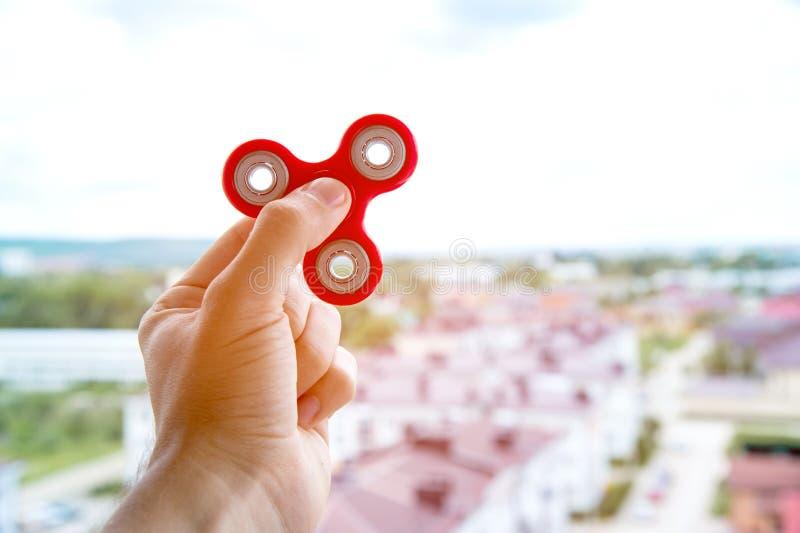 手使用与锭床工人以在城市坐立不安的手玩具的都市风景为背景 免版税库存图片