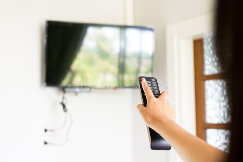 手使用在电视遥控开-关方式下 免版税库存照片