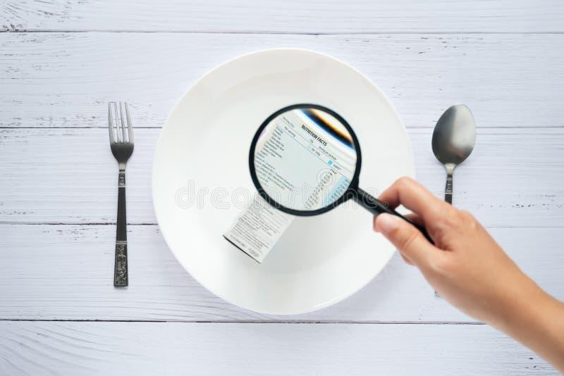 手使用放大镜放大看营养事实的细节标记在消费品箱子一边 库存照片
