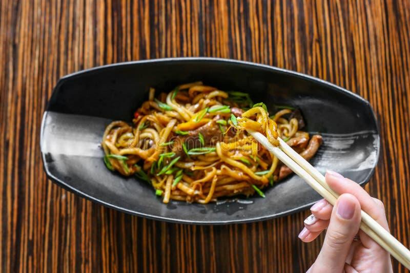 手使用筷子对提取鲜美面条 r 免版税库存照片