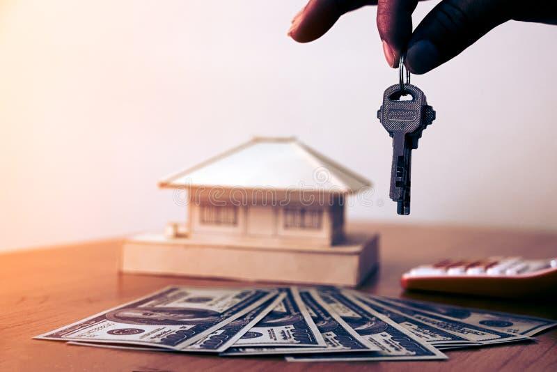 手供以人员把握与金钱和小屋的房子关键 免版税库存照片