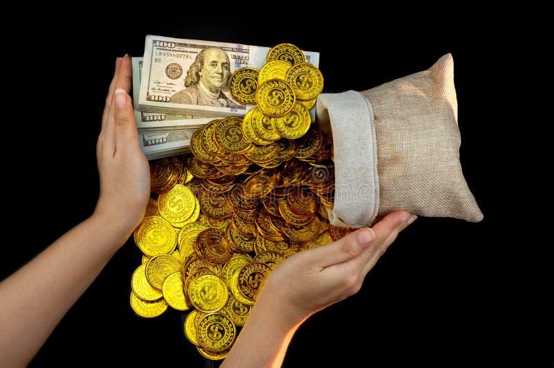 手保护在珍宝大袋和堆捆绑的金币100张美元钞票 库存照片