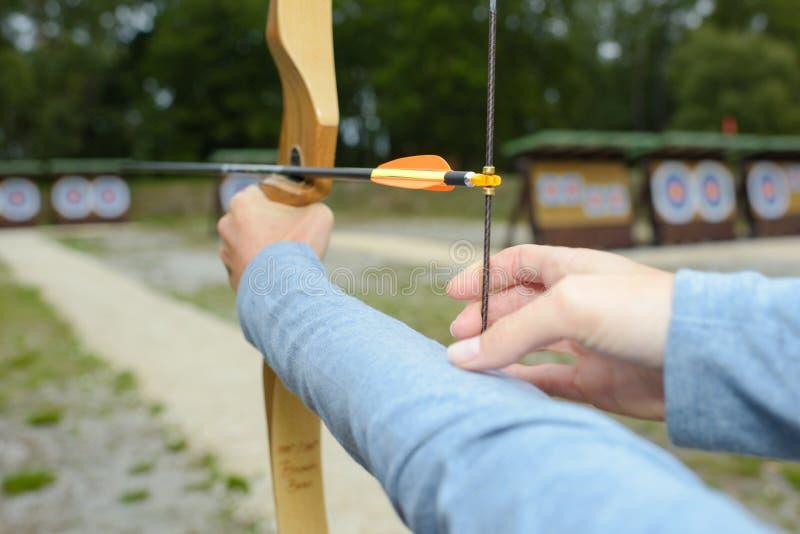 手保持平衡把串弓箭向后拉 免版税库存图片