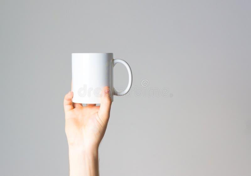 手停滞咖啡杯手中,布局,在白色背景,嘲笑,自由空间, 免版税库存图片