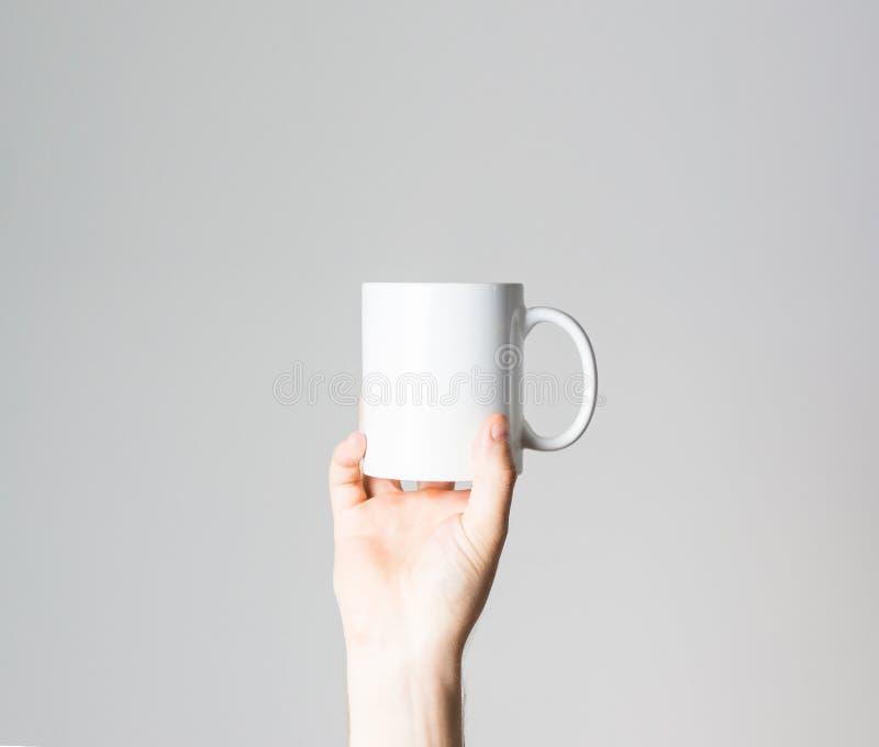 手停滞咖啡杯手中,布局,在白色背景,嘲笑,自由空间, 免版税图库摄影